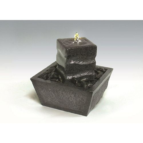 Fontaine de relaxation illuminée avec pillier de granit et des pierres naturelles.